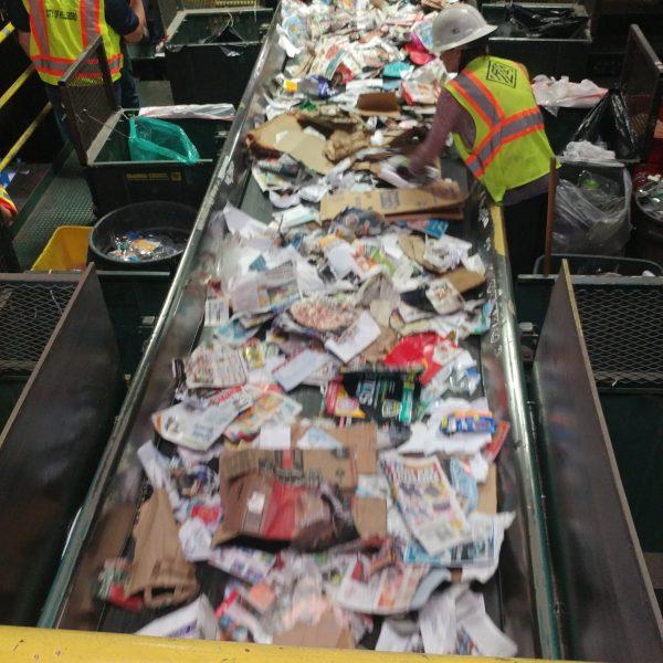 Man sorting materials at recycling facility