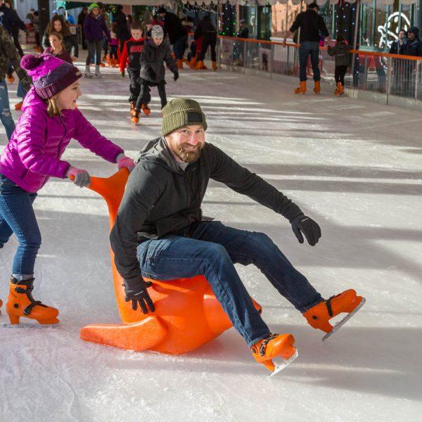Man and girl ice skating at Winter Village