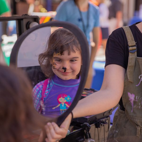 Young girl with face paint looking at reflection in mirror